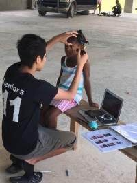 Mission volunteer examining the eyes of a young girl.