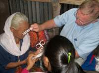 Dr. Curtis using the refraction kit to examine a patient's eyes.